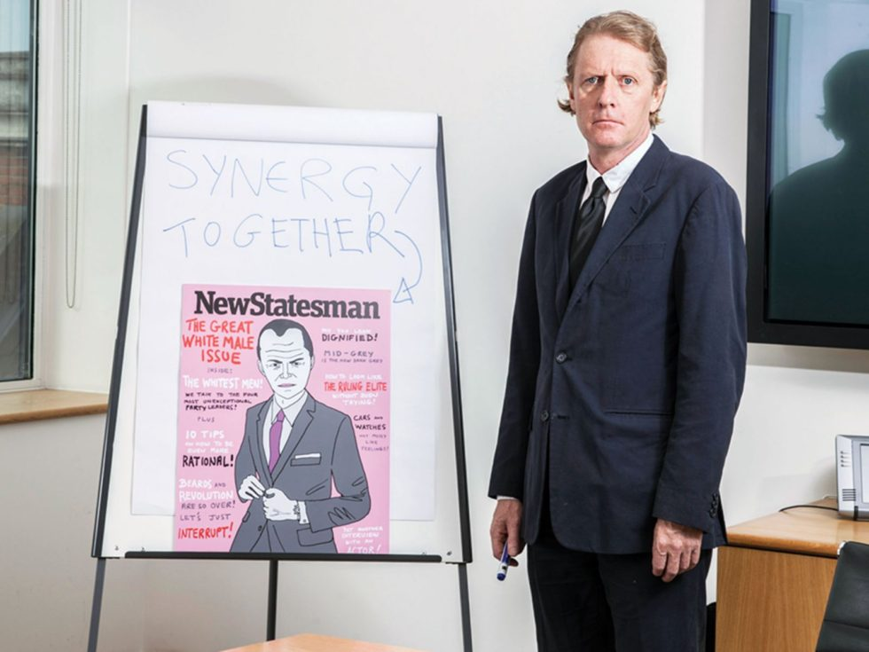 A light skinned man in a suit stands next to a white flip board with a copy of a New Statesmen cover for The Default Man article.