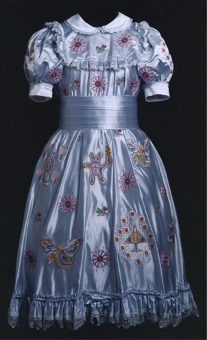 A blue satin dress ebroidered with flowers, war planes, teddy bears and hermaphroditic butterflies
